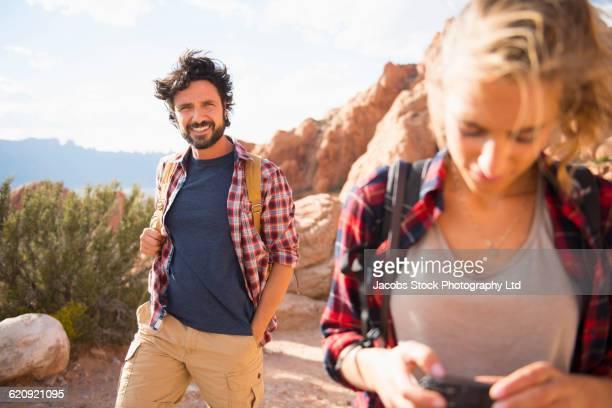 Hispanic couple hiking on remote trail