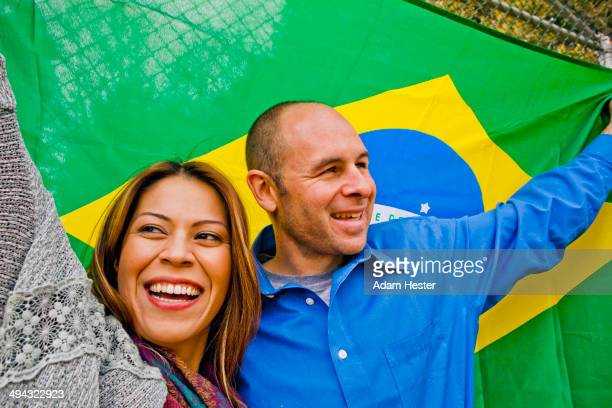 hispanic couple holding brazilian flag - südamerika stock-fotos und bilder