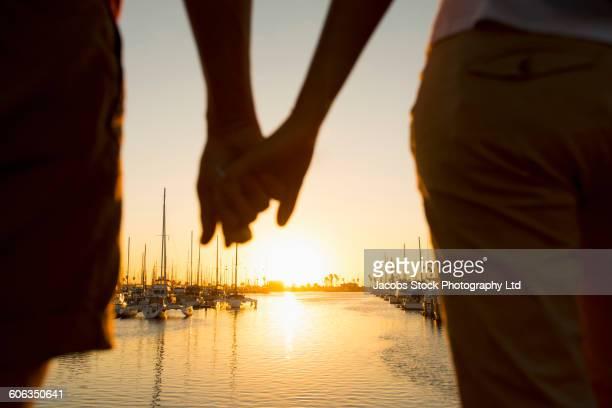 Hispanic couple holding hands at marina