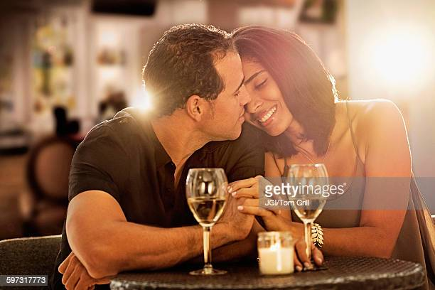 Hispanic couple holding hands at restaurant