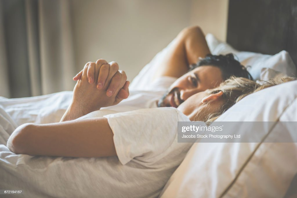 Hispanic couple holding hands in bed : Stockfoto