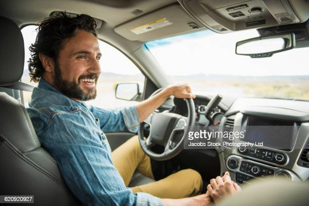 hispanic couple holding hands in car - driver stock pictures, royalty-free photos & images