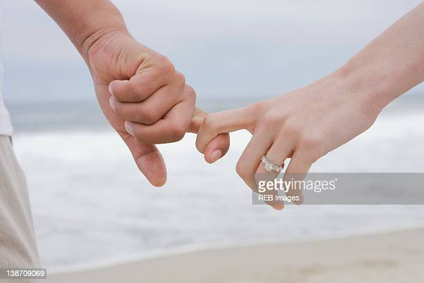 Hispanic couple holding hands on beach