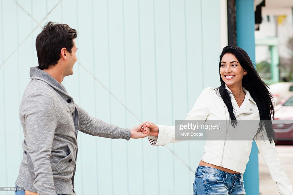 Hispanic couple holding hands outdoors : Foto stock