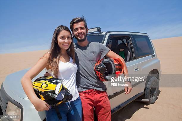 Hispanic couple holding helmets leaning on sports utility vehicle