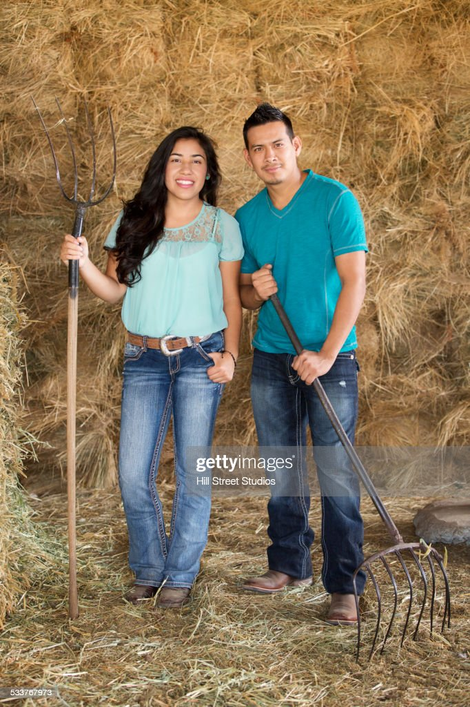 Hispanic couple holding pitchforks near hay in barn : Foto stock