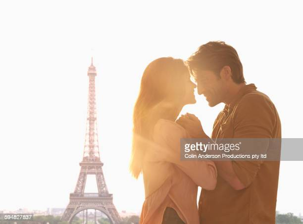 Hispanic couple hugging at Eiffel Tower, Paris, Ile