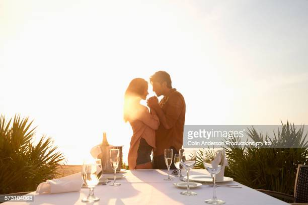 Hispanic couple hugging at table outdoors