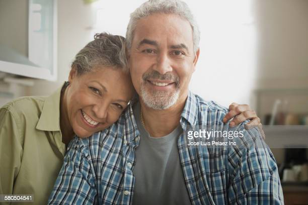 hispanic couple hugging in kitchen - 60 69 anos imagens e fotografias de stock