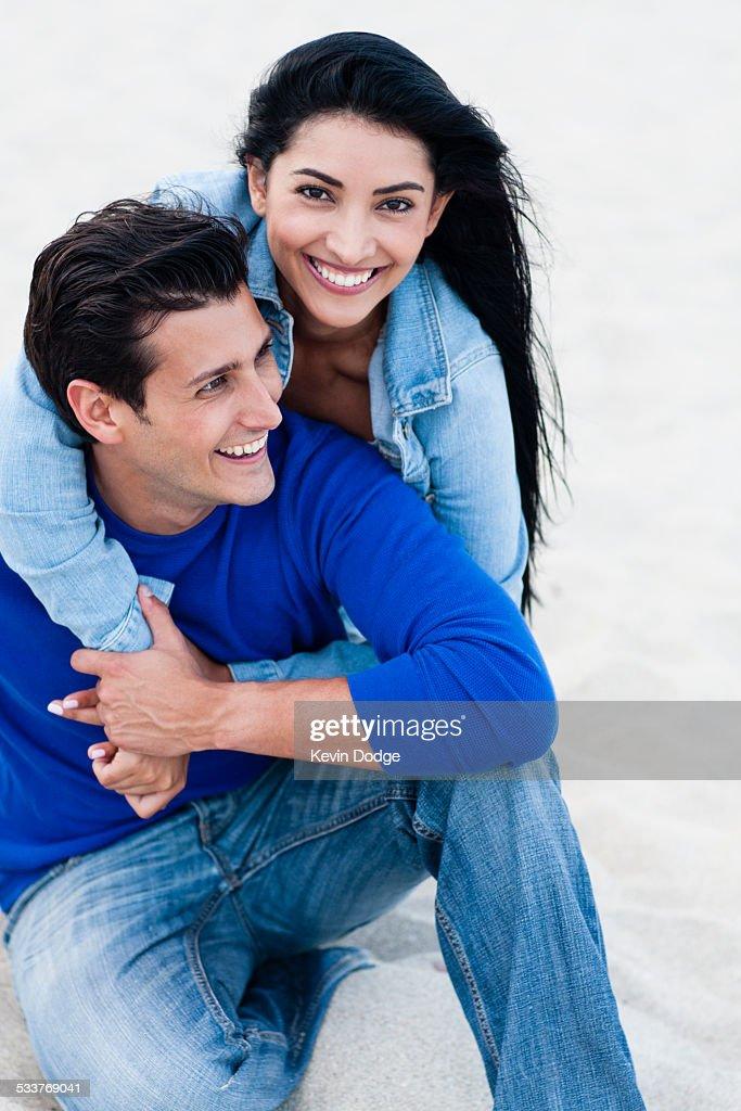 Hispanic couple hugging on beach : Foto stock