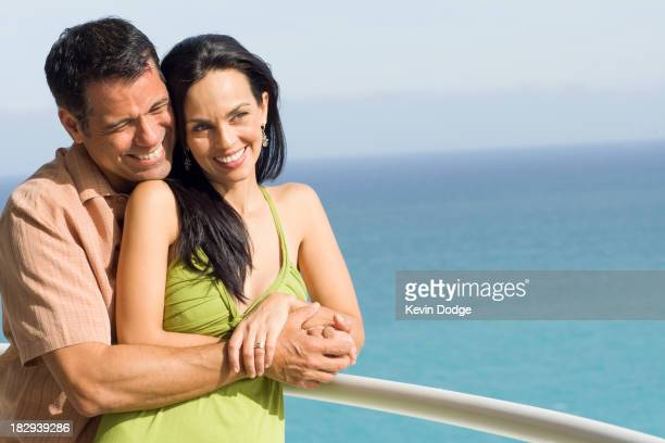Hispanic couple hugging on boat deck