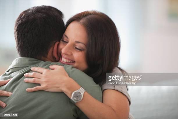 Hispanic couple hugging on sofa