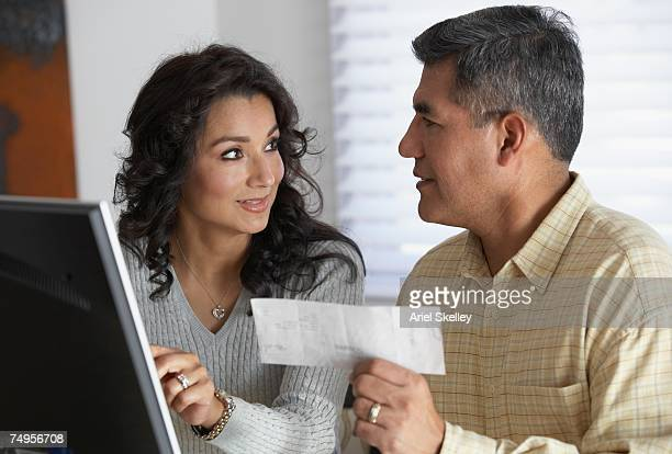 hispanic couple in front of computer - bank account stock pictures, royalty-free photos & images
