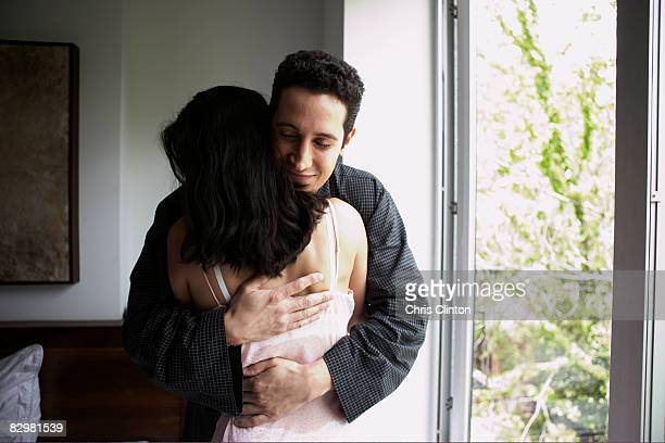 Hispanic couple in luxury bedroom, embracing
