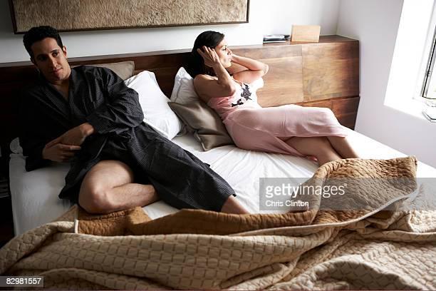 Hispanic couple in luxury bedroom, marital discord