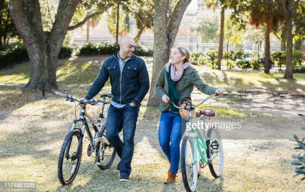 hispanic couple in the park, riding bicycles - next to stock pictures, royalty-free photos & images