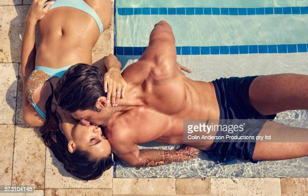 Hispanic couple kissing at swimming pool