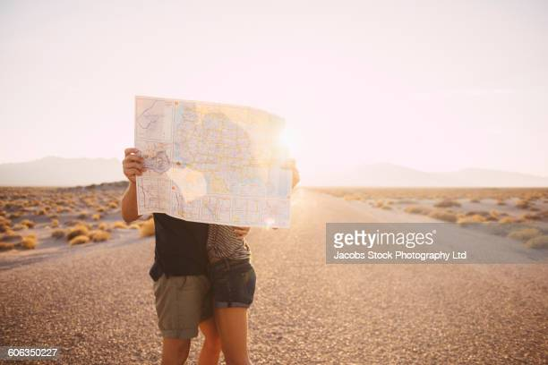 Hispanic couple kissing behind map on remote road