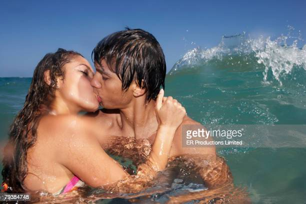 hispanic couple kissing in ocean - kissing on the mouth stock photos and pictures