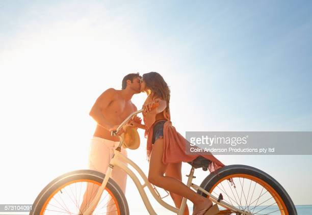 Hispanic couple kissing on bicycle on beach