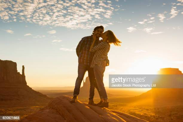 Hispanic couple kissing on rock formation in remote desert