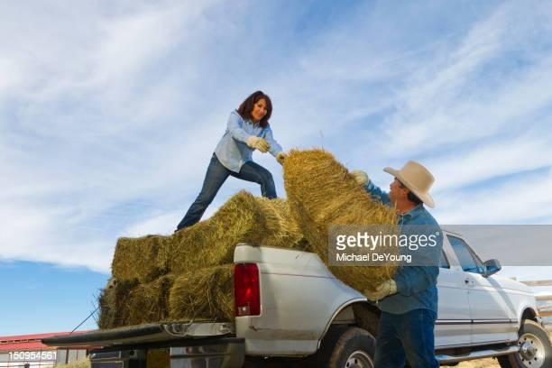 Hispanic couple loading hay onto truck