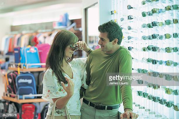 Hispanic Couple Looking at Sunglasses in an Airport's Duty Free Shop