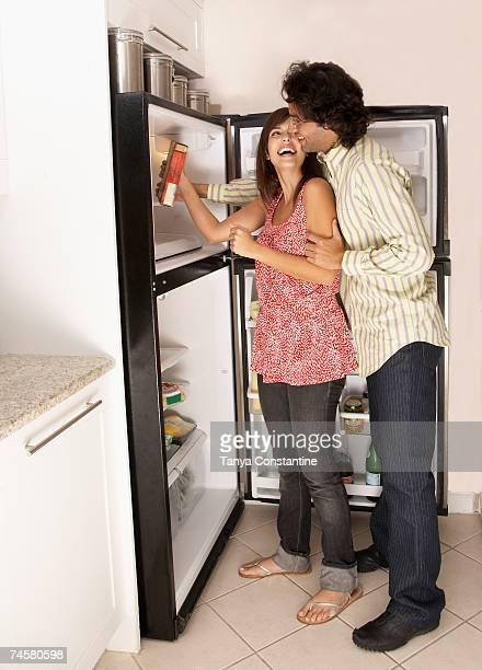 Hispanic couple looking in refrigerator