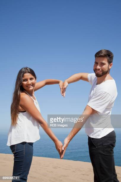 Hispanic couple making heart-shape with arms at beach