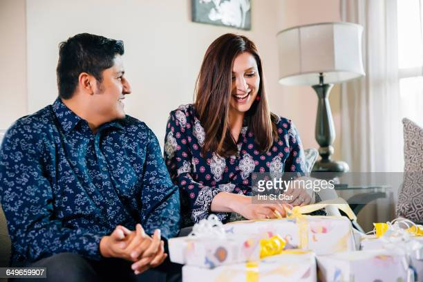 Hispanic couple opening gifts at baby shower