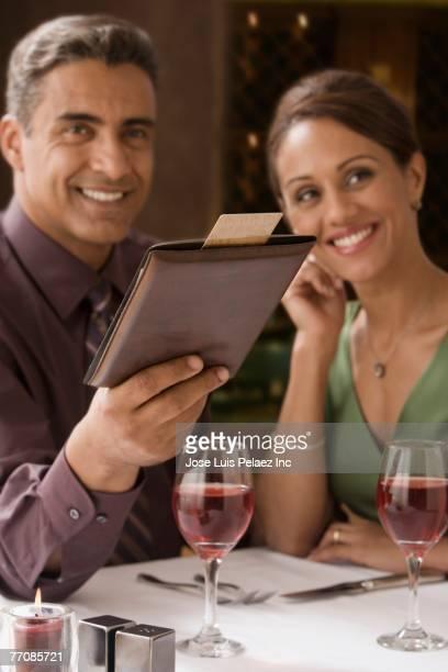 Hispanic couple paying bill at restaurant