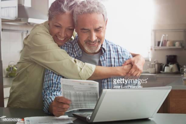 Hispanic couple paying bills on laptop