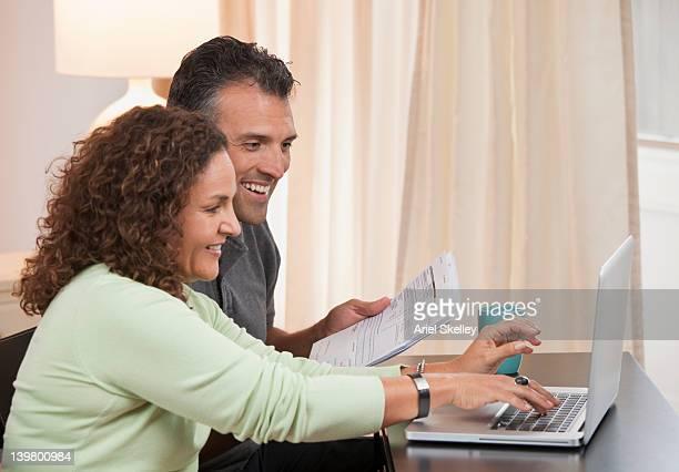 Hispanic couple paying bills together online