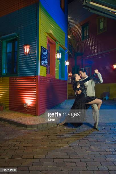 Hispanic couple performing tango on city street