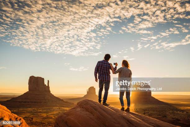 hispanic couple photographing remote desert - us kultur stock-fotos und bilder