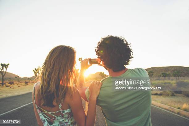 Hispanic couple photographing sunset in street