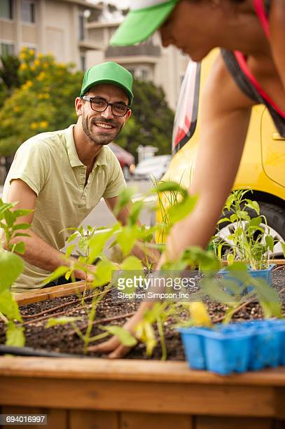 Hispanic couple planting in raised garden