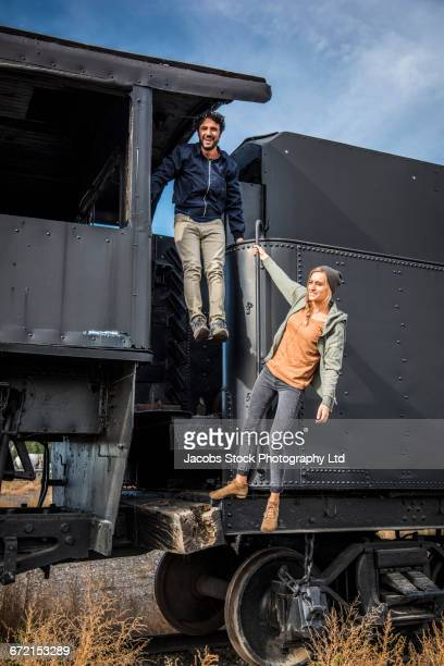 Hispanic couple playing on train exterior