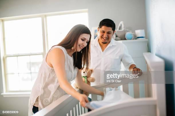 Hispanic couple preparing crib bed in nursery