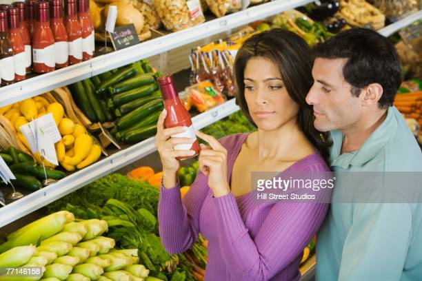 Hispanic couple reading label in grocery store