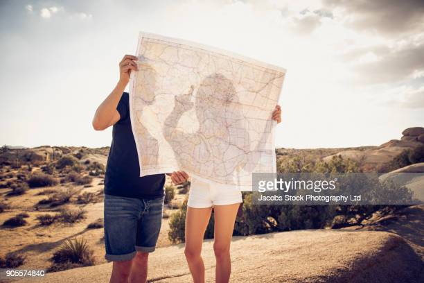 hispanic couple reading map in desert - us map stock photos and pictures