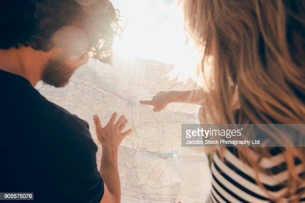 Hispanic couple reading map in desert
