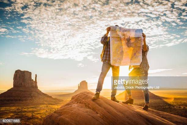 hispanic couple reading map in remote desert - us map stock photos and pictures