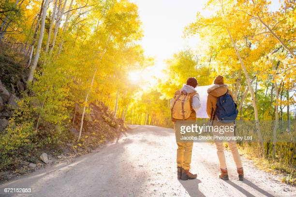 Hispanic couple reading map on hiking path
