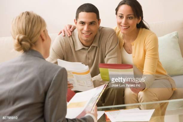 Hispanic couple receiving financial consultation