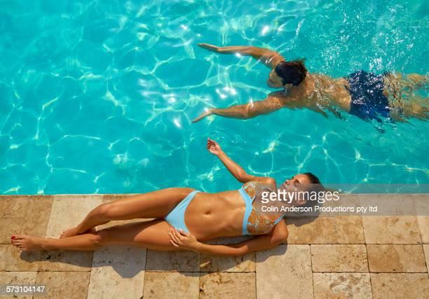 hispanic couple relaxing at swimming pool - tomando sol - fotografias e filmes do acervo