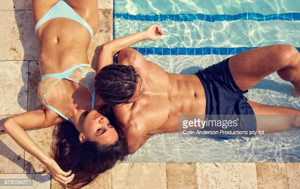 Hispanic couple relaxing at swimming pool