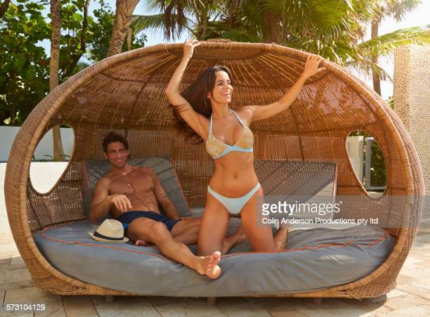 Hispanic couple relaxing in cabana