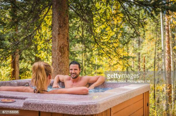 hispanic couple relaxing in hot tub - hot tub stock pictures, royalty-free photos & images