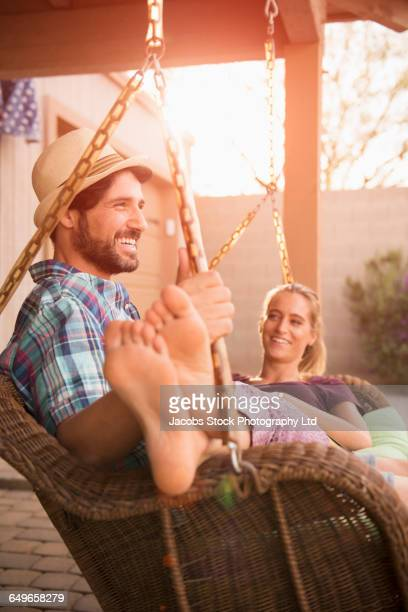 Hispanic couple relaxing in porch swing